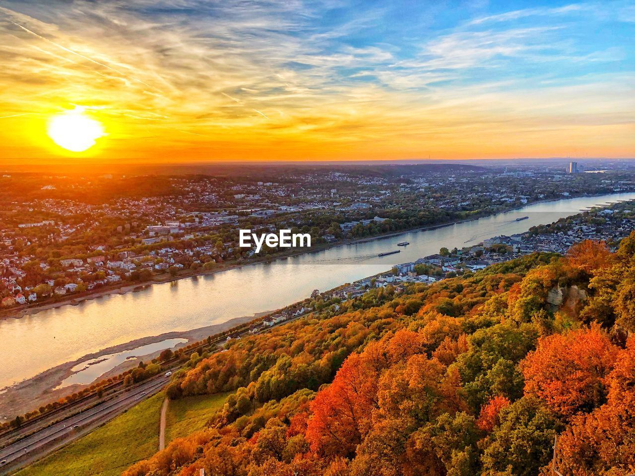 Scenic view of river amidst city during sunset