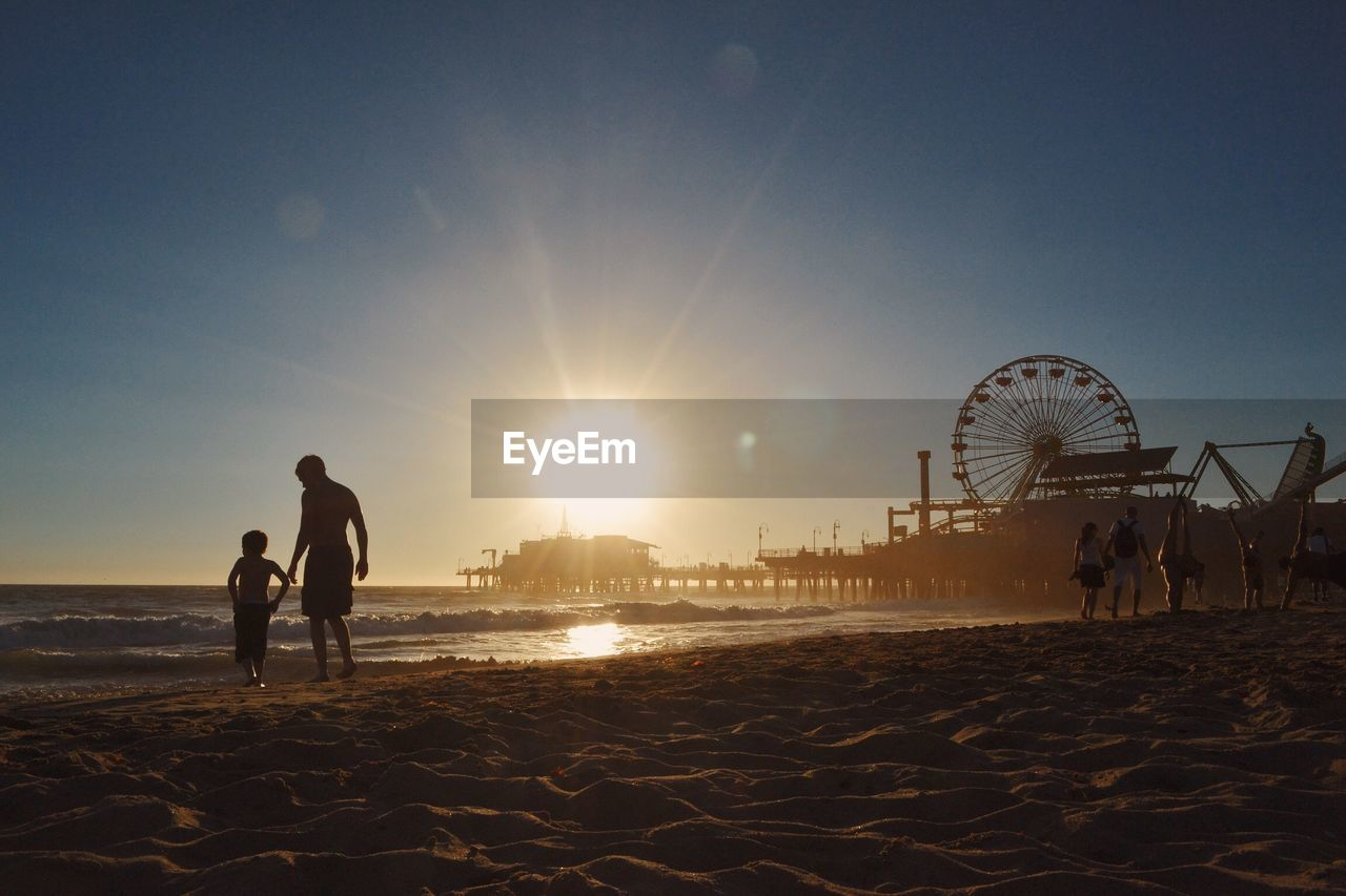 People Walking At Beach By Santa Monica Pier Against Clear Sky During Sunset