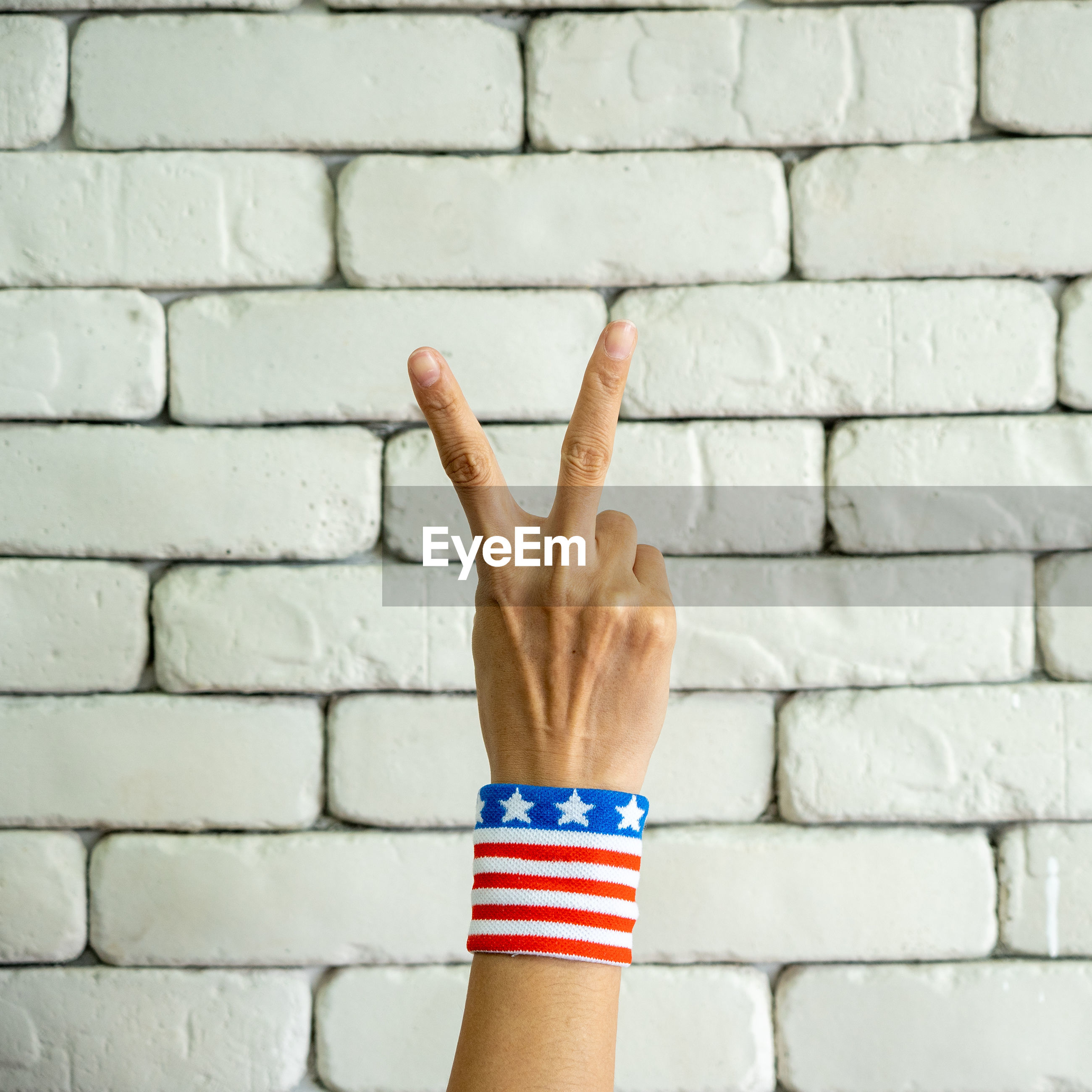 Cropped hand gesturing against brick wall