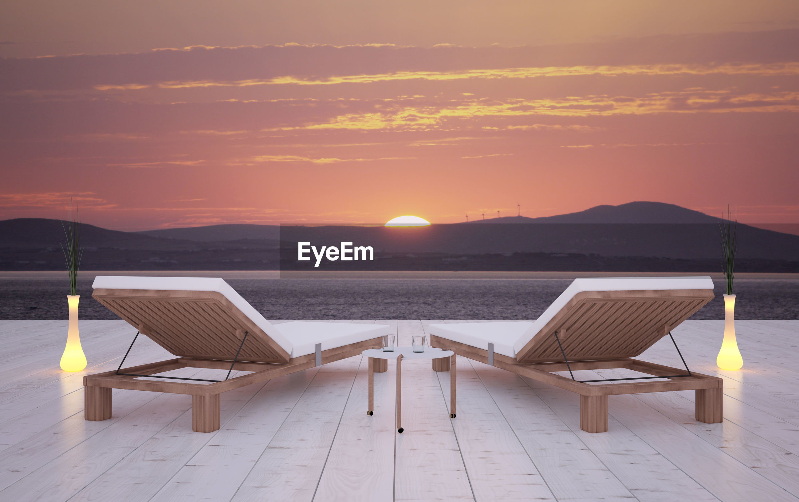 Chaise longue by sea against sky during sunset