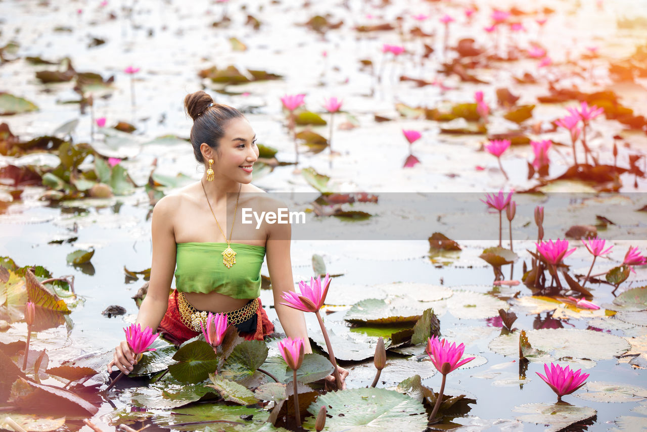 Smiling woman amidst lotus flowers in pond