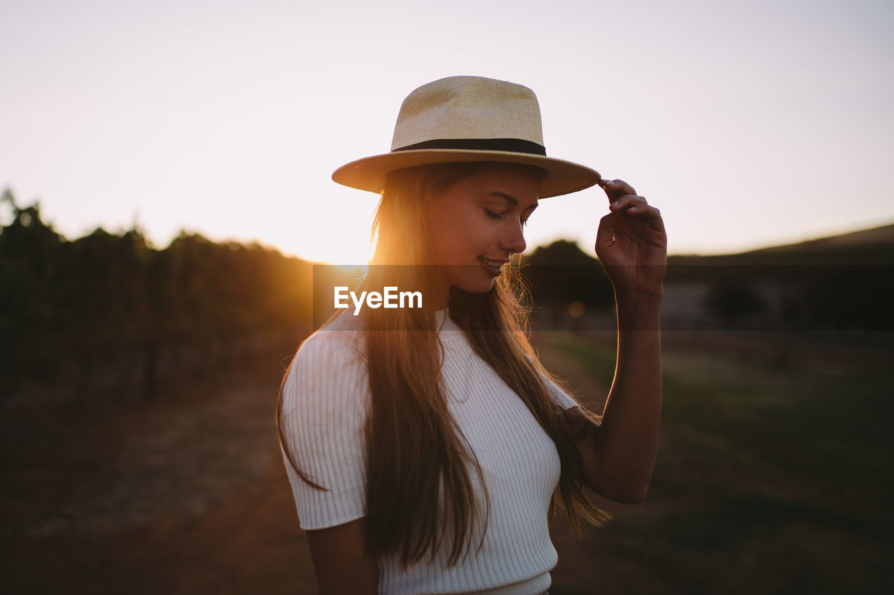 Young Woman Wearing Hat Standing Against Sky During Sunset