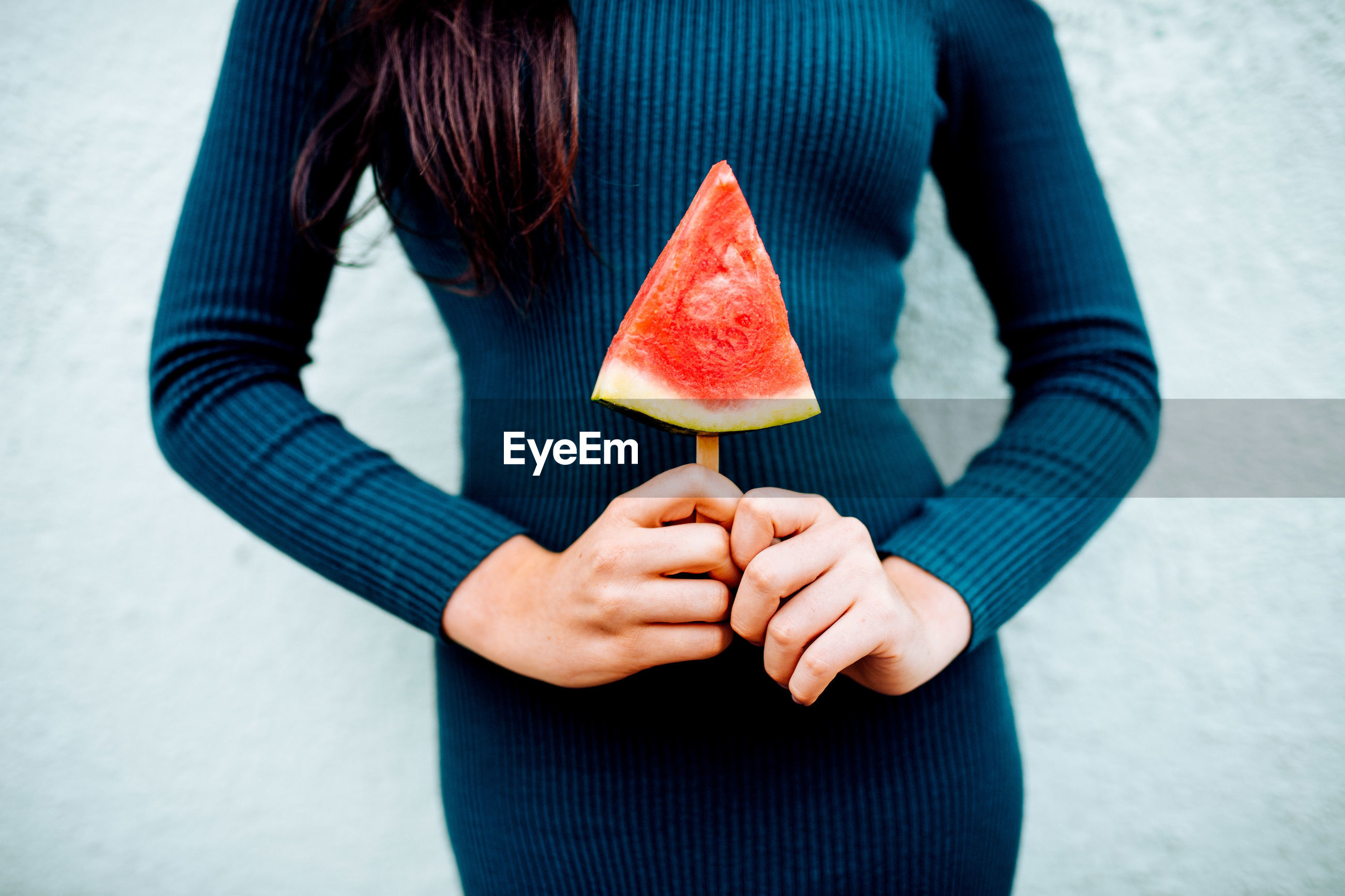 Woman holding watermelon slice on a stick