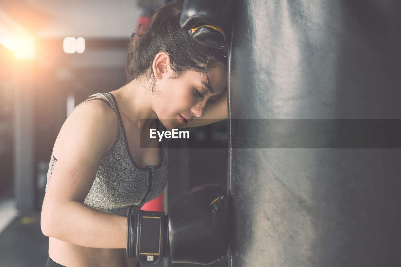 Tired female athlete training with punching bag in gym
