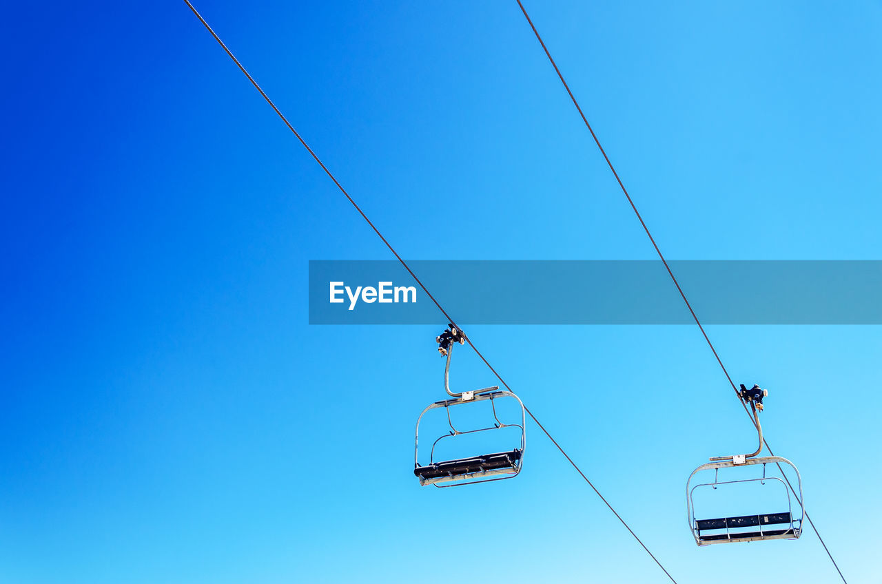 Low Angle View Of Overhead Cable Cars Against Clear Blue Sky