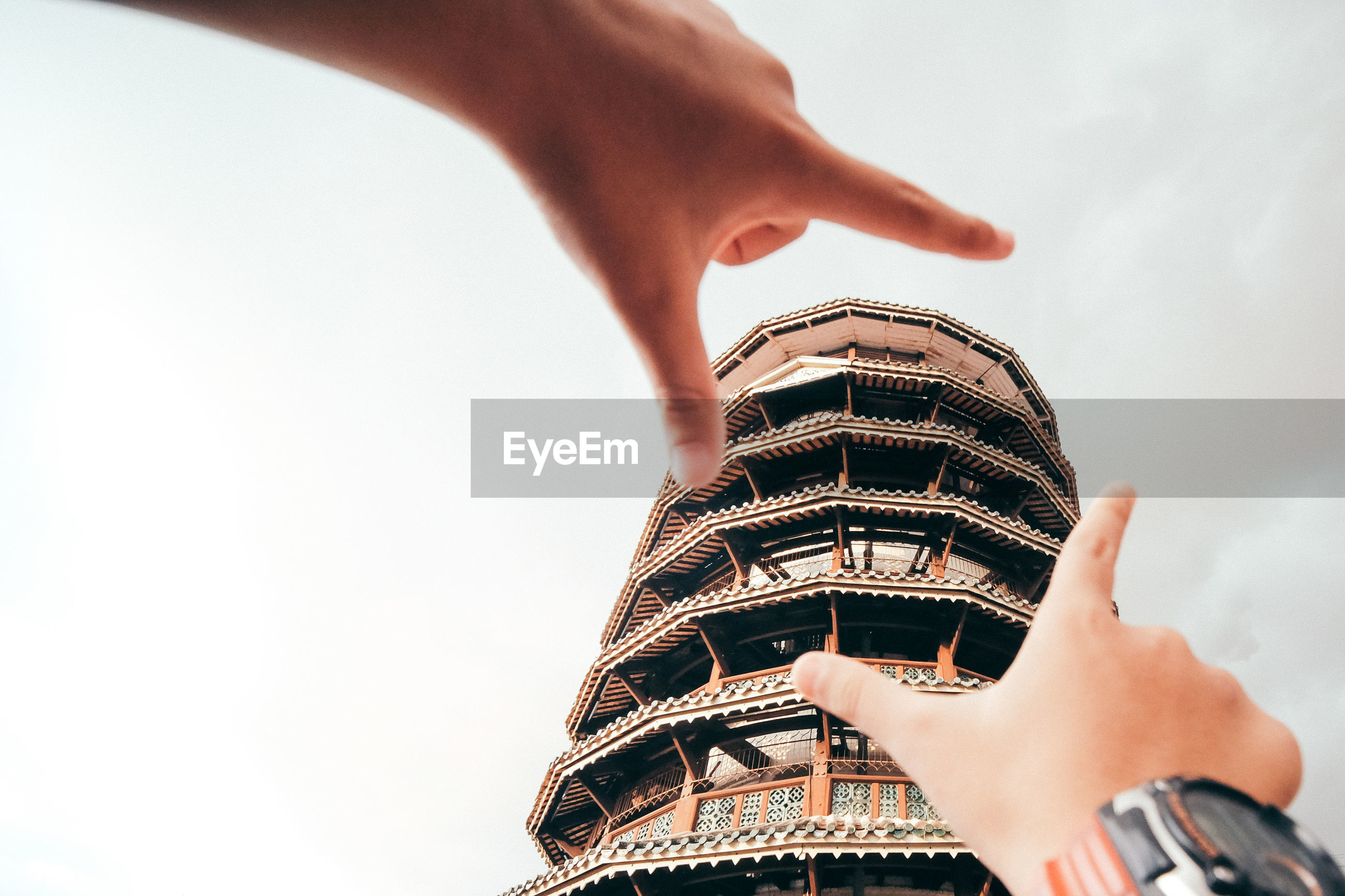LOW ANGLE VIEW OF HAND HOLDING BUILDING