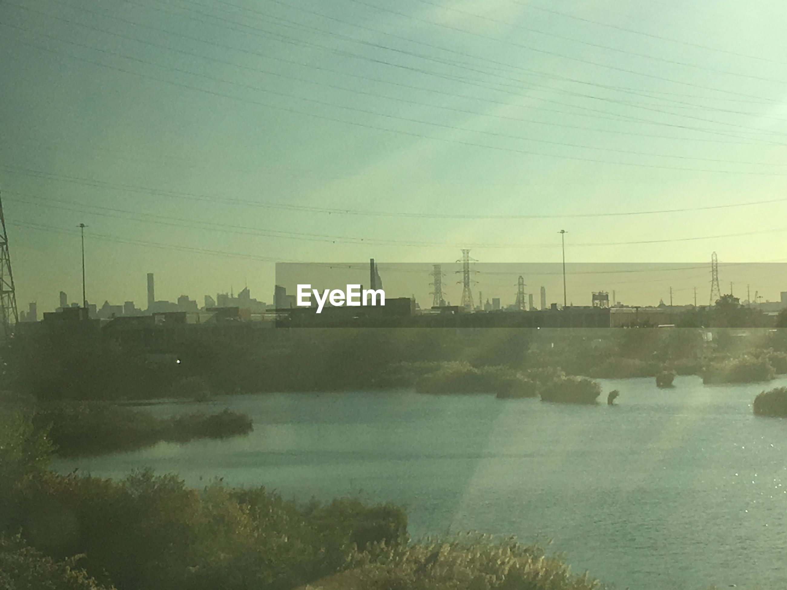 water, river, no people, nature, sky, outdoors, built structure, electricity pylon, day, riverbank, architecture, building exterior, smoke stack, landscape, industry, beauty in nature, tree, factory, city, power station, cityscape