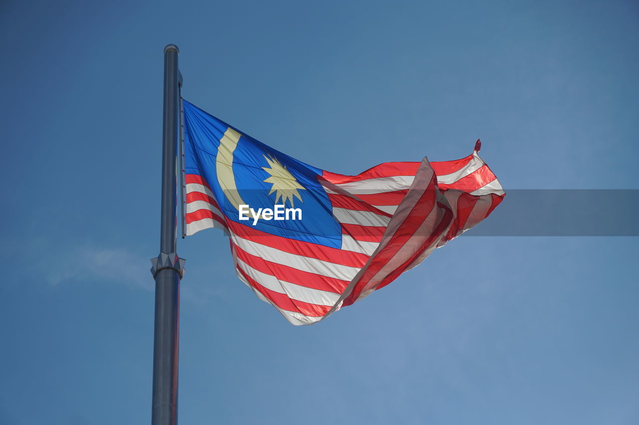 Low angle view of malaysian flag against blue sky