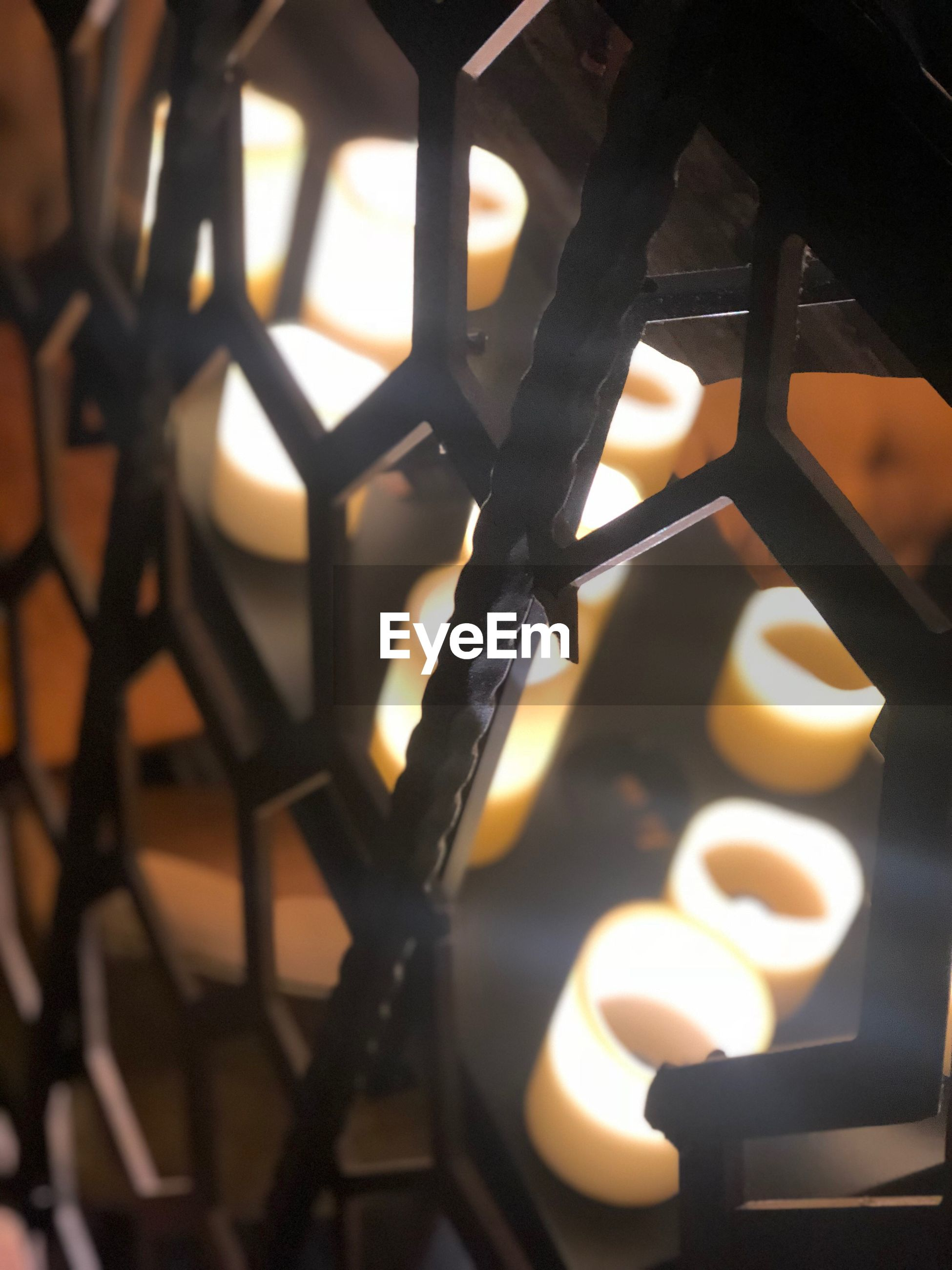 High angle view of tea light candles seen through metal railing
