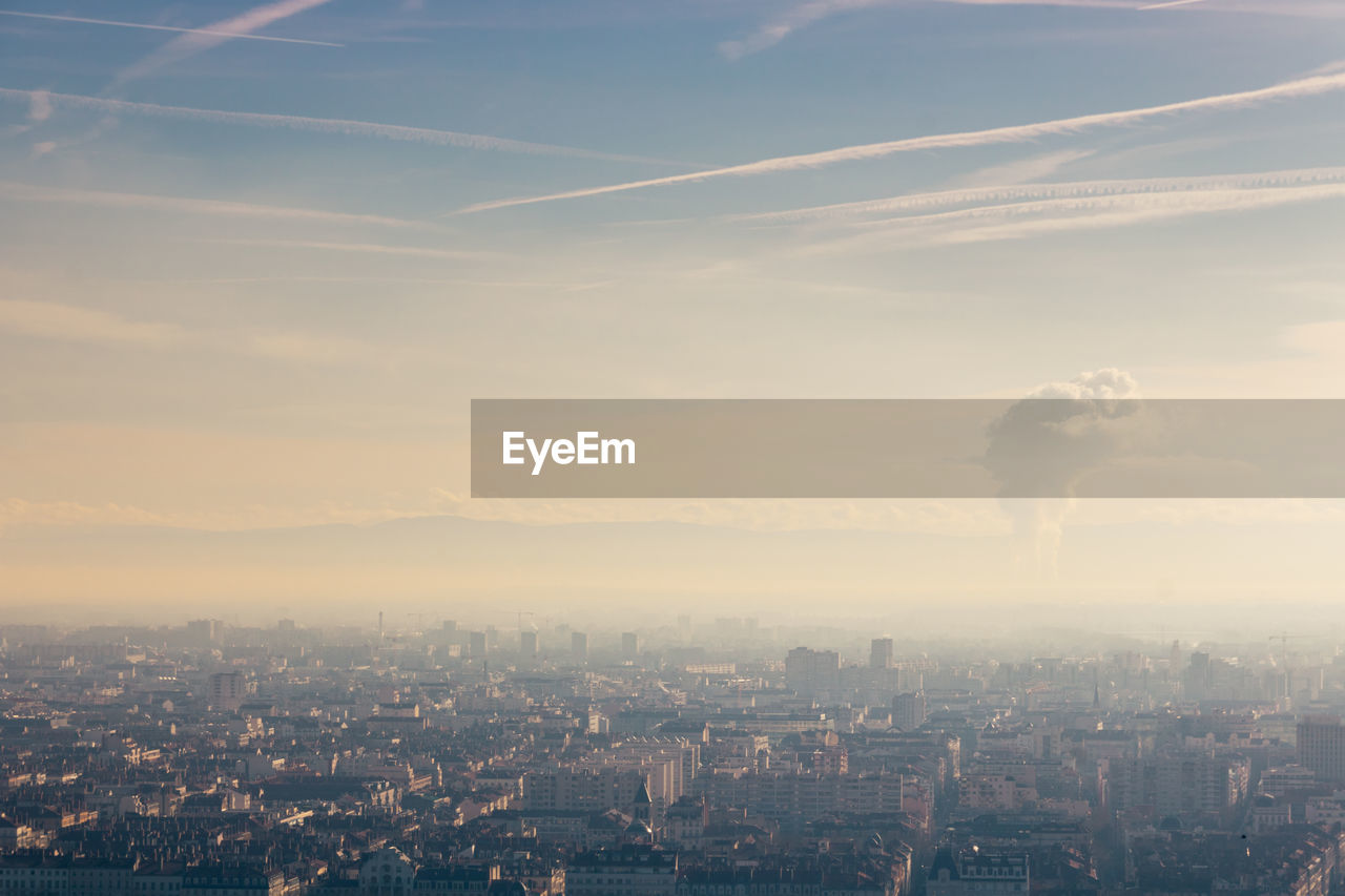 Aerial view of city and air pollution against sky during sunset