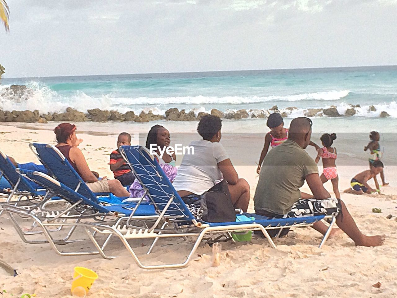 beach, sea, sand, horizon over water, vacations, sitting, enjoyment, water, weekend activities, relaxation, beauty in nature, men, outdoors, leisure activity, day, lifestyles, summer, large group of people, togetherness, nature, women, adult, sky, friendship, scenics, wave, people, adults only