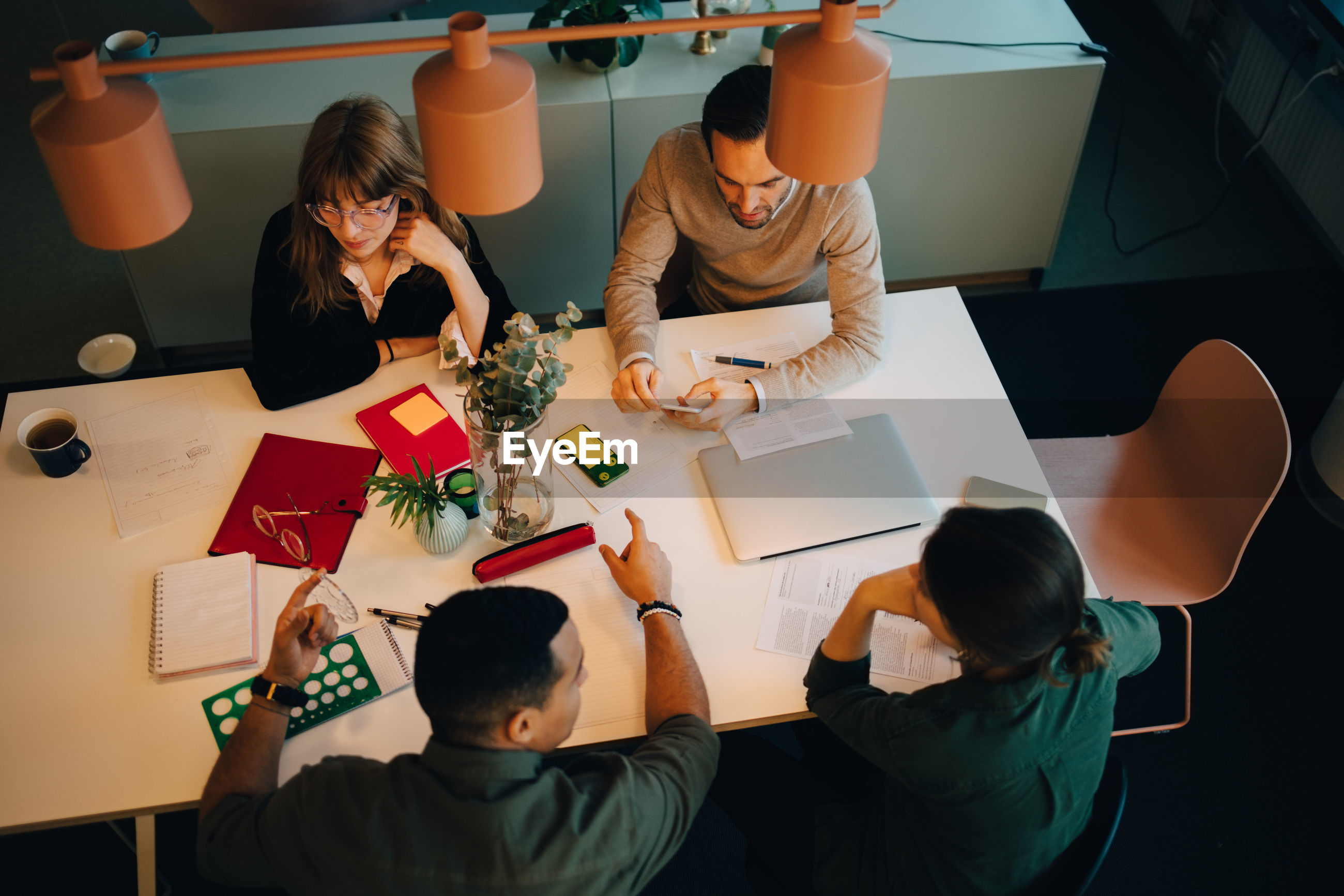 High angle view of multi-ethnic business team discussing while sitting at desk in creative office