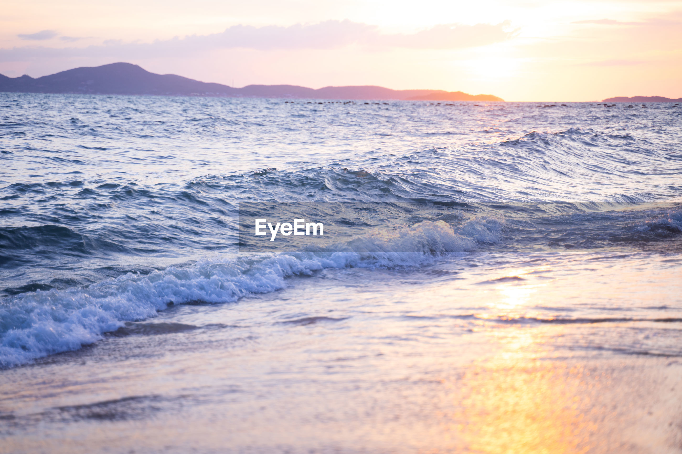 SCENIC VIEW OF SEA WAVES RUSHING TOWARDS SHORE DURING SUNSET