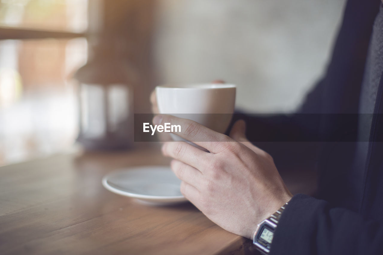 Cropped Image Of Businessman Having Coffee While Sitting At Table