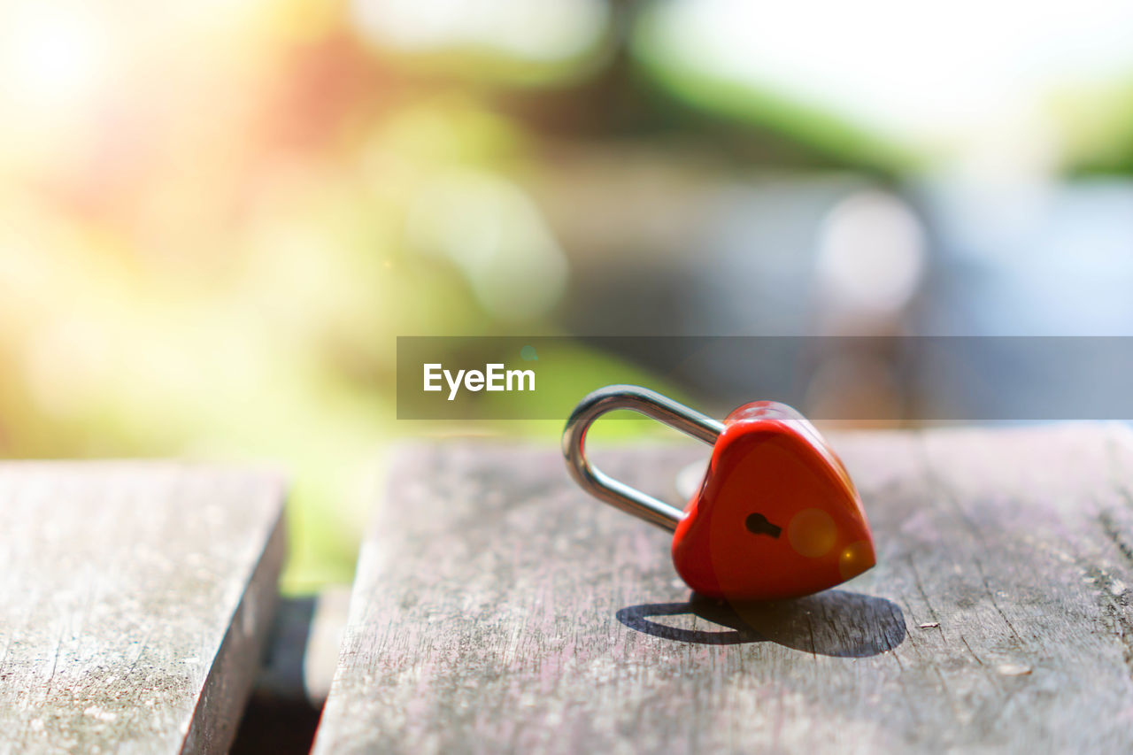 selective focus, close-up, wood - material, no people, red, day, focus on foreground, solid, still life, outdoors, nature, metal, rock, table, rock - object, love, emotion, sunlight, positive emotion, heart shape