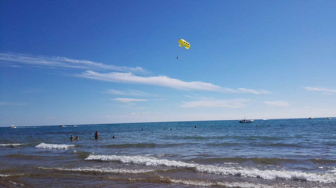 sea, adventure, extreme sports, leisure activity, water, beach, nature, sport, sky, wave, beauty in nature, horizon over water, scenics, outdoors, parachute, vacations, real people, motion, day, skill, lifestyles, flying, one person, paragliding, people