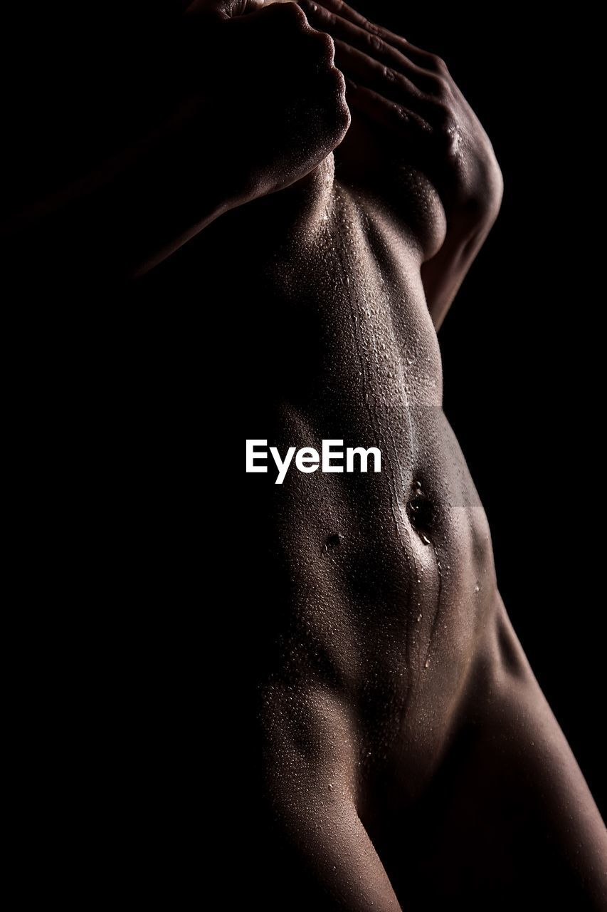 black background, studio shot, one person, indoors, lifestyles, midsection, human body part, shirtless, men, muscular build, adult, body part, skin, males, human skin, strength, standing, dark, masculinity, abdominal muscle, human face