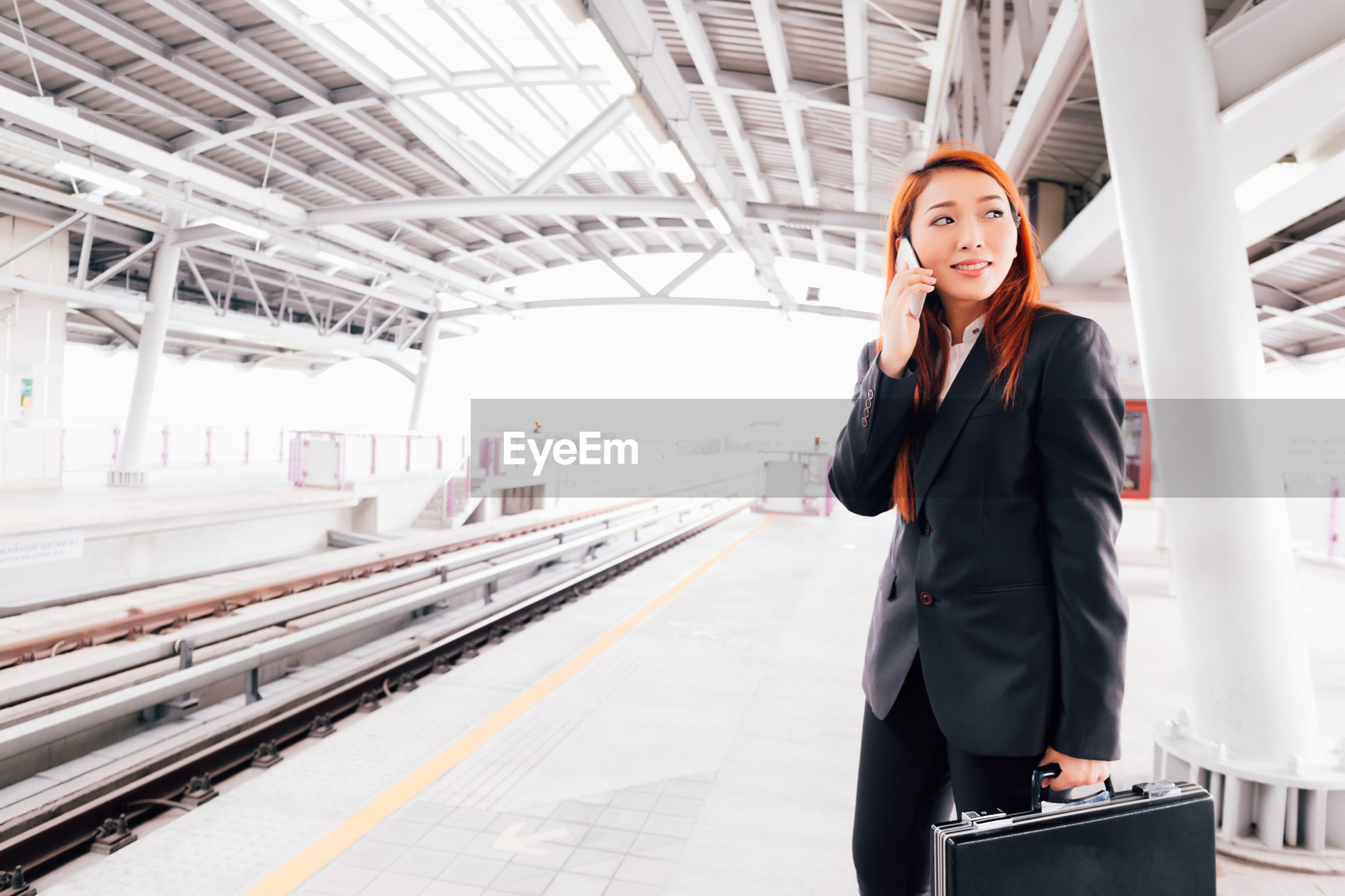 Businesswoman using phone while standing on railroad station platform