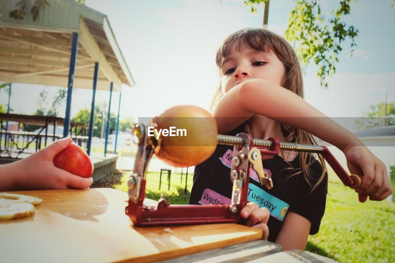 Cute girl holding fruit peeler on table outdoors