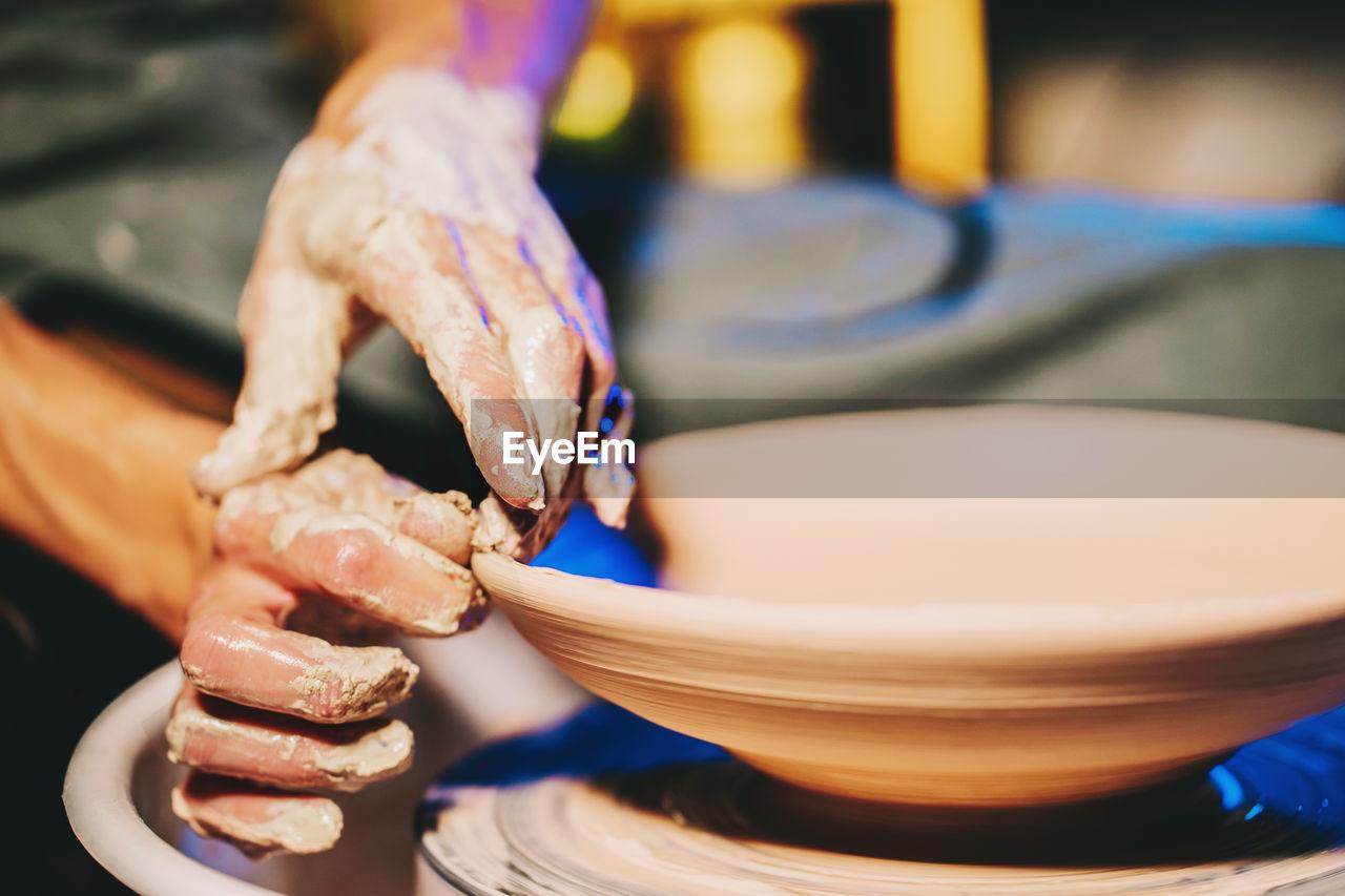Cropped Hands Of Potter Making Pot In Pottery Workshop