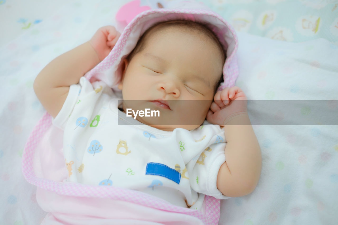 High angle view of cute baby girl sleeping on bed at home