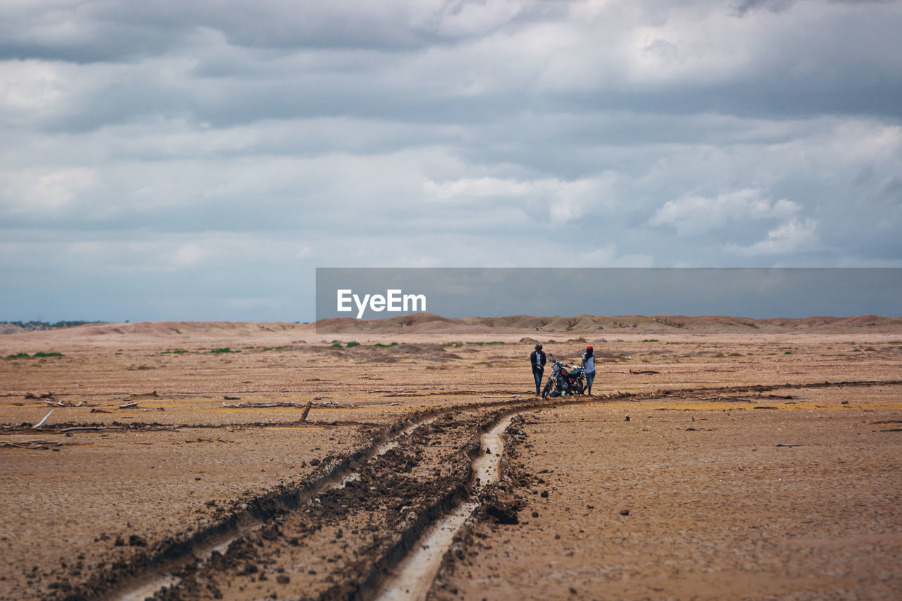 sky, cloud - sky, landscape, environment, nature, land, scenics - nature, day, transportation, people, men, non-urban scene, two people, field, beauty in nature, real people, horizon over land, tranquil scene, tranquility, walking, outdoors, riding