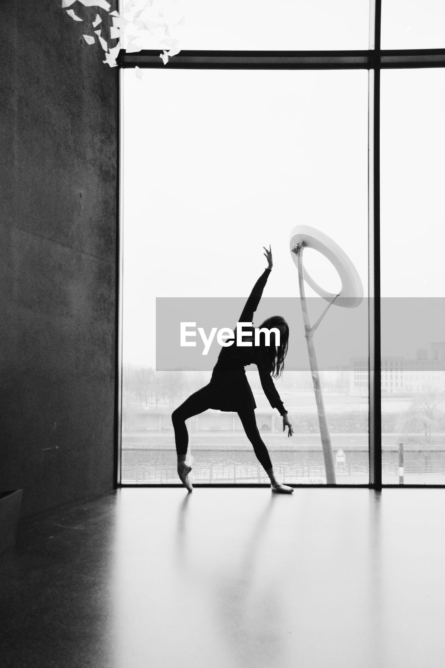 FULL LENGTH SIDE VIEW OF WOMAN WALKING ON WINDOW