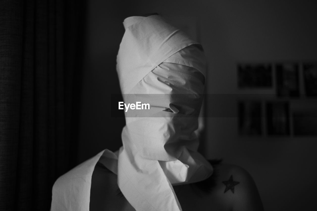 Close-up of person with face wrapped in clothe at home