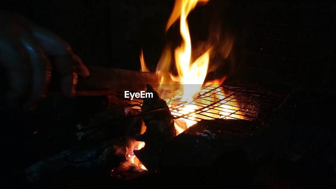 heat - temperature, flame, fire, burning, fire - natural phenomenon, log, wood - material, firewood, orange color, glowing, wood, nature, night, bonfire, motion, real people, indoors, fireplace, one person, close-up, hand, campfire, dark