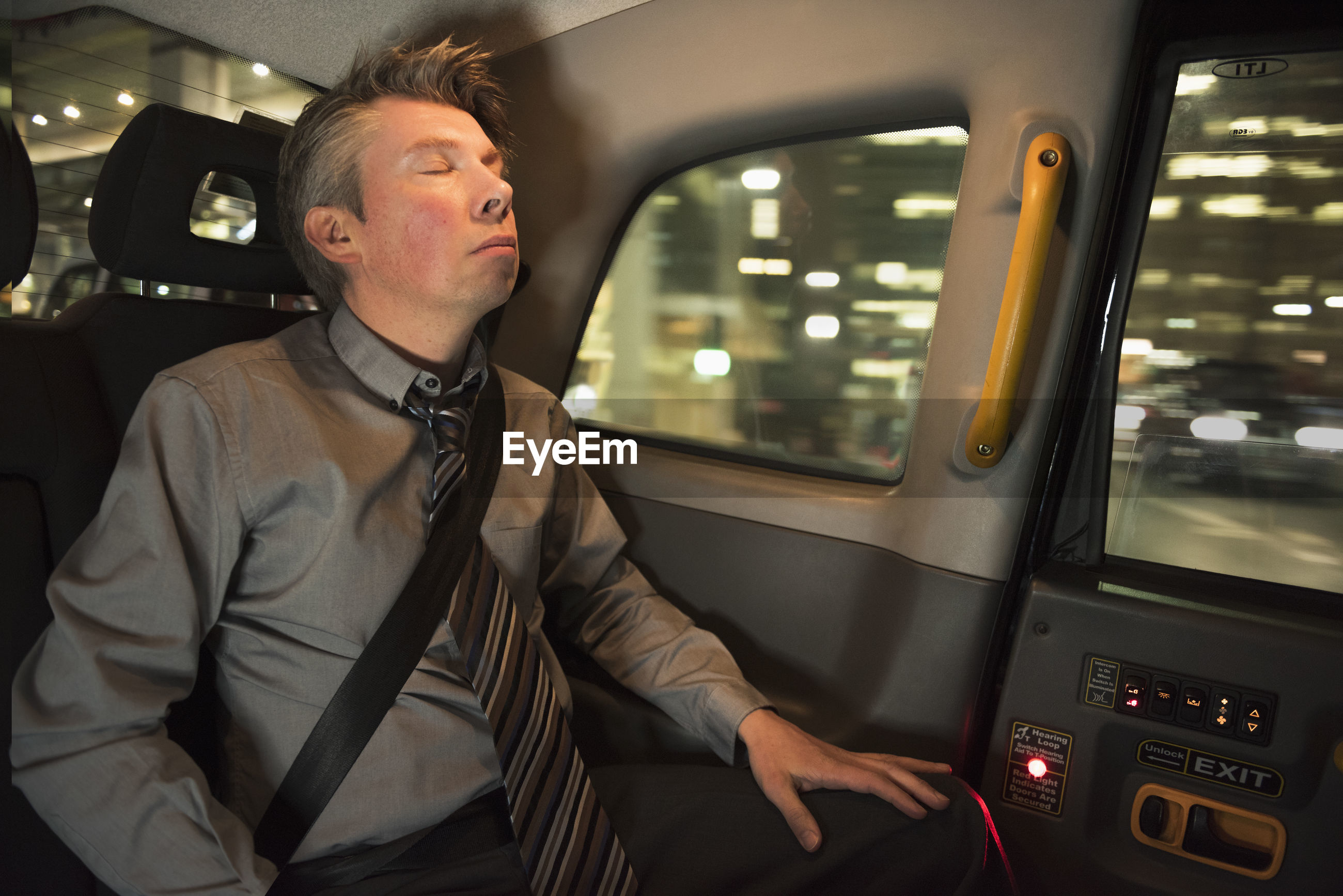 Man sitting with eyes closed in car