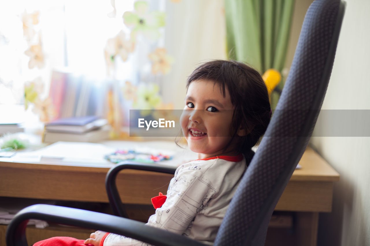 Portrait of smiling girl sitting on chair at home
