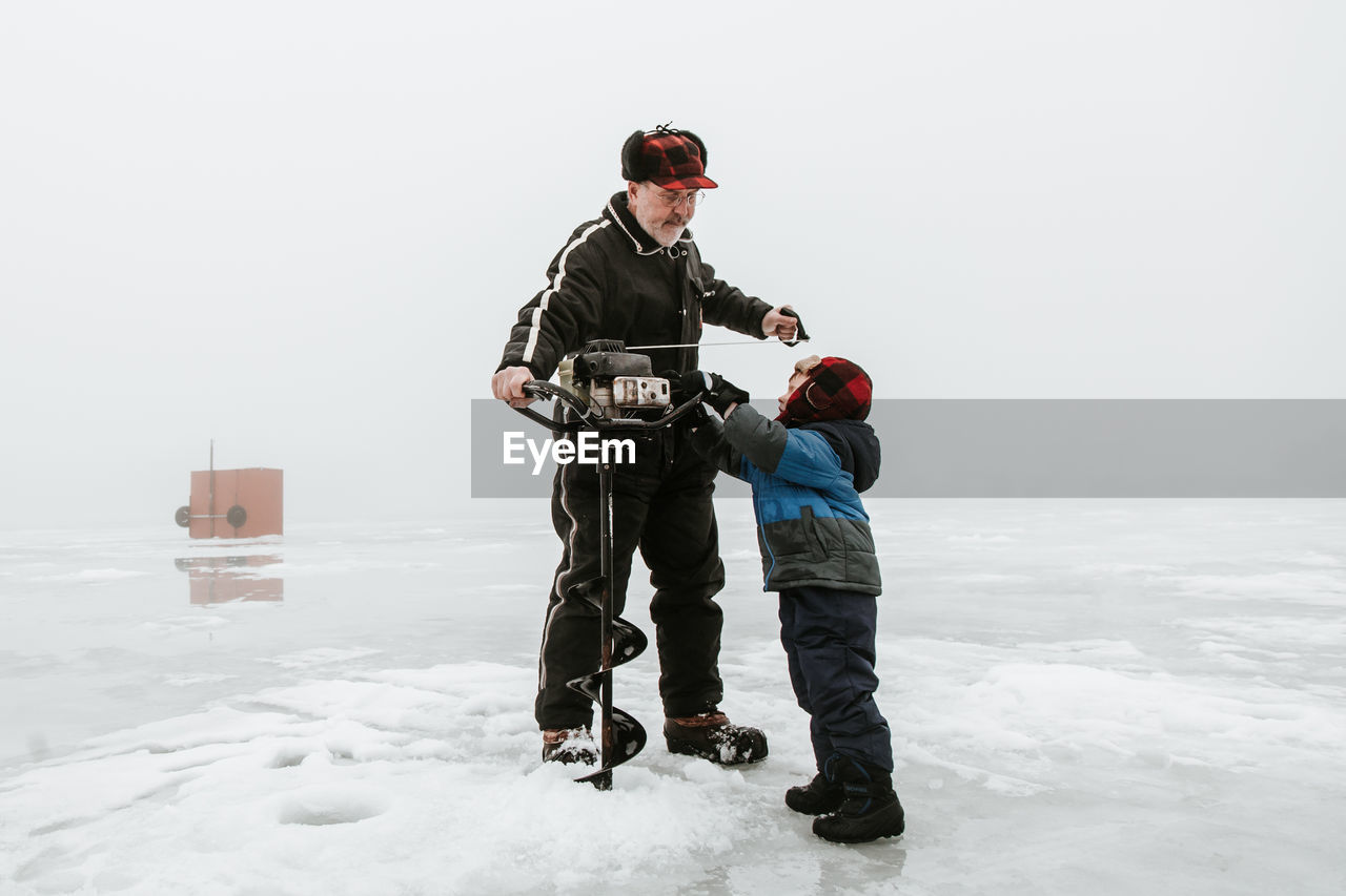 Grandfather And Grandson Making Hole In Ice Rink
