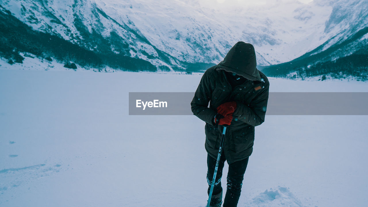 Man with hiking pole standing on snow covered mountain