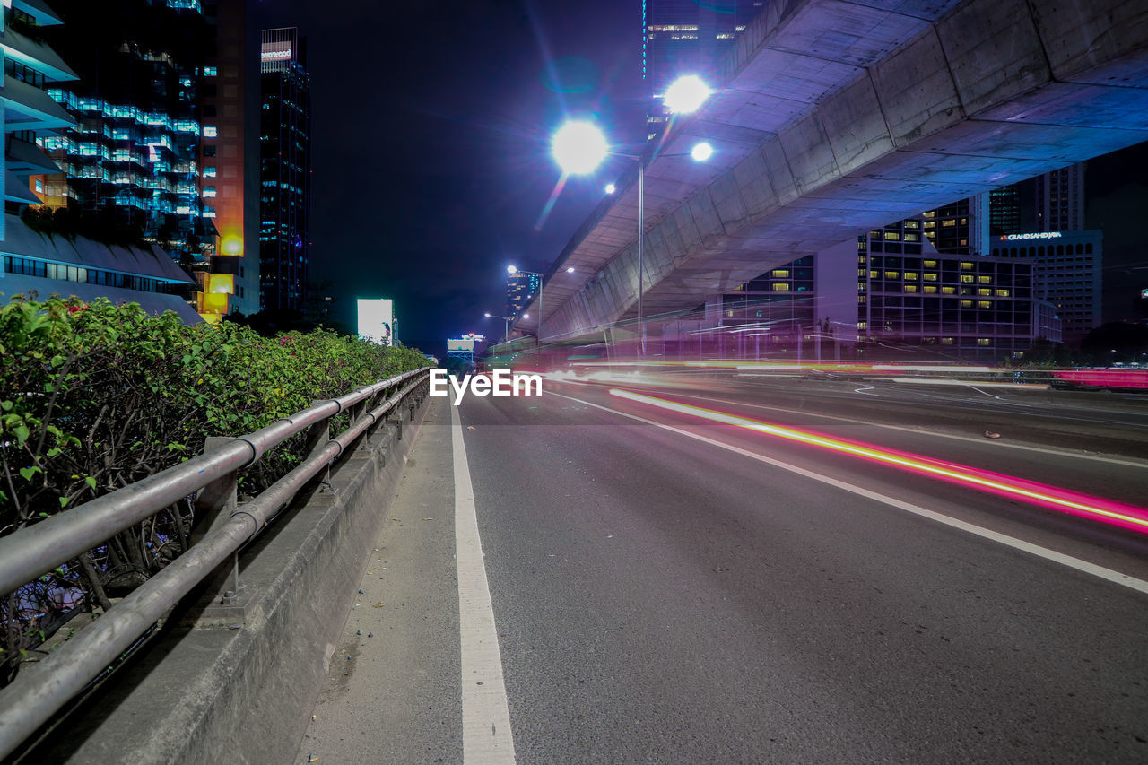 LIGHT TRAILS ON STREET AMIDST BUILDINGS IN CITY AT NIGHT