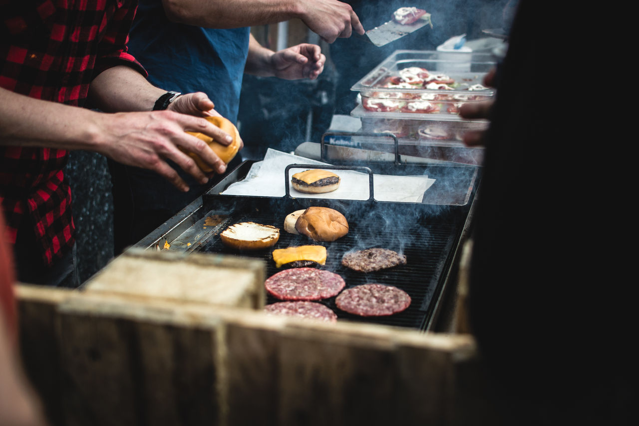 Midsection Of Person Cooking Meat On Barbecue
