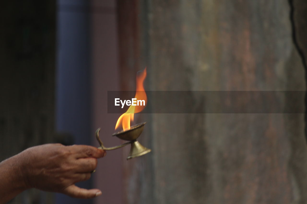 Cropped Hand Of Man Holding Burning Diya During Religious Ceremony