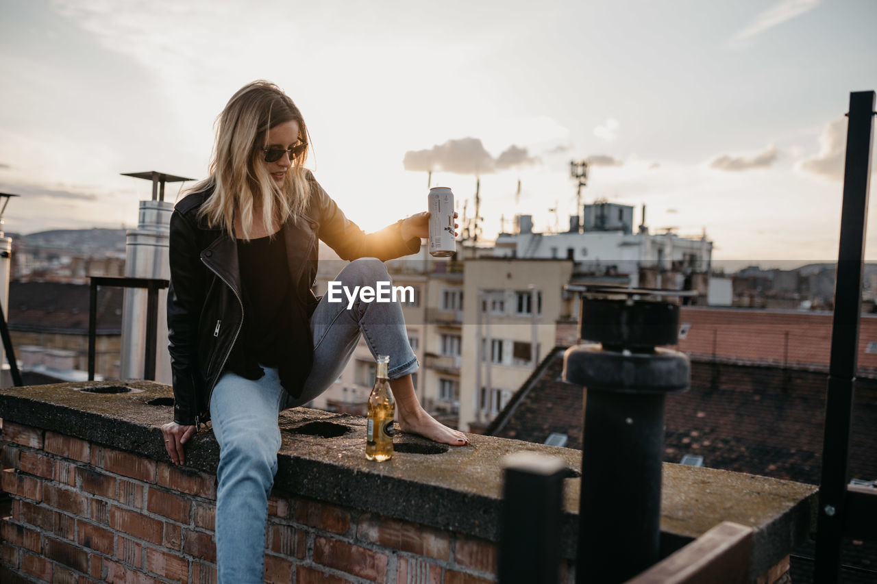 Woman In Sunglasses Having Drink While Sitting On Retaining Wall In City