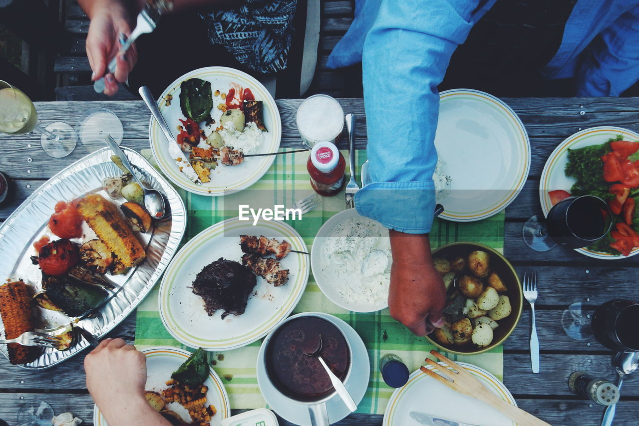 Cropped Image Of People Having Food At Table