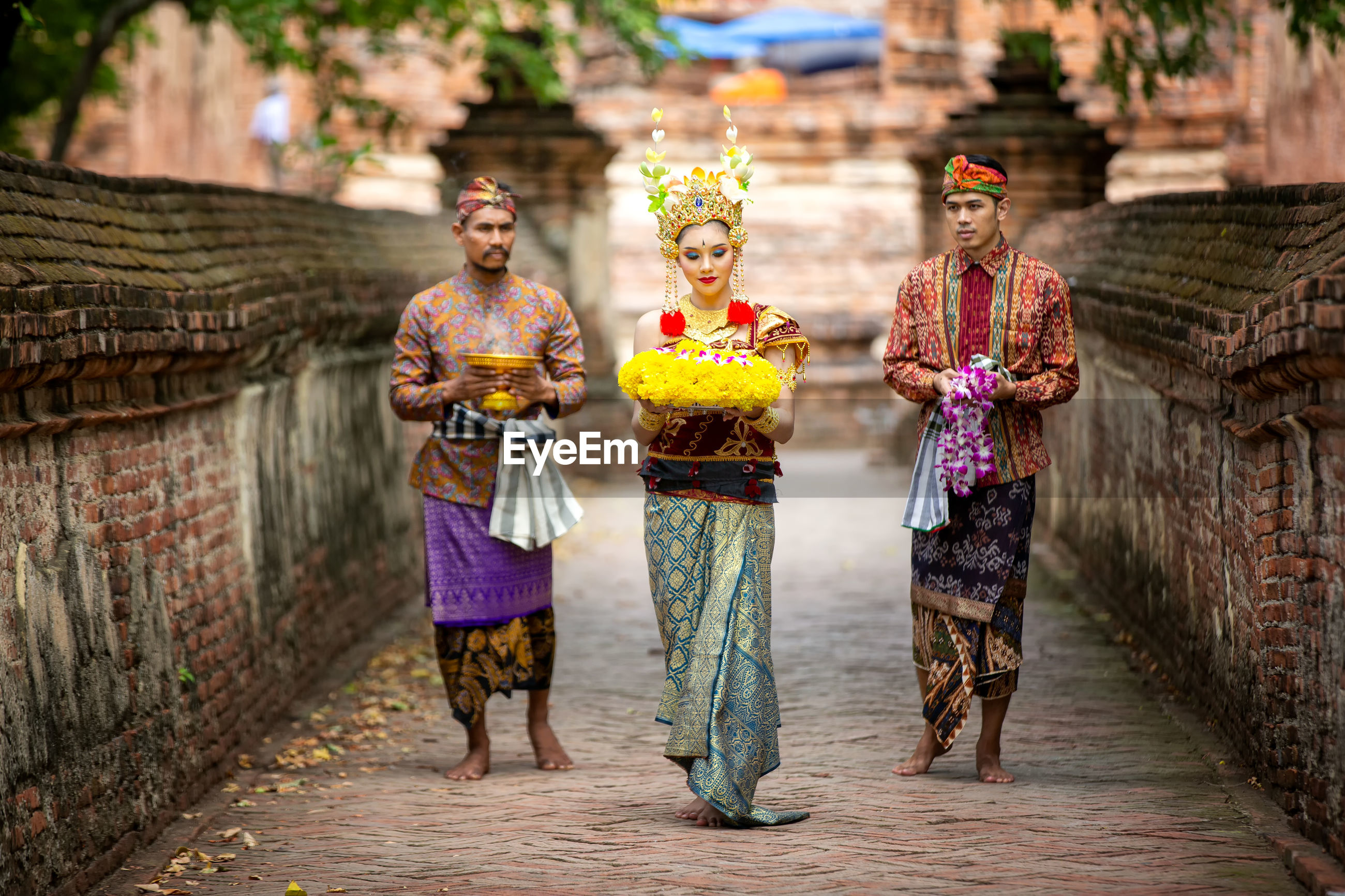 Men and woman with religious offerings walking on footpath
