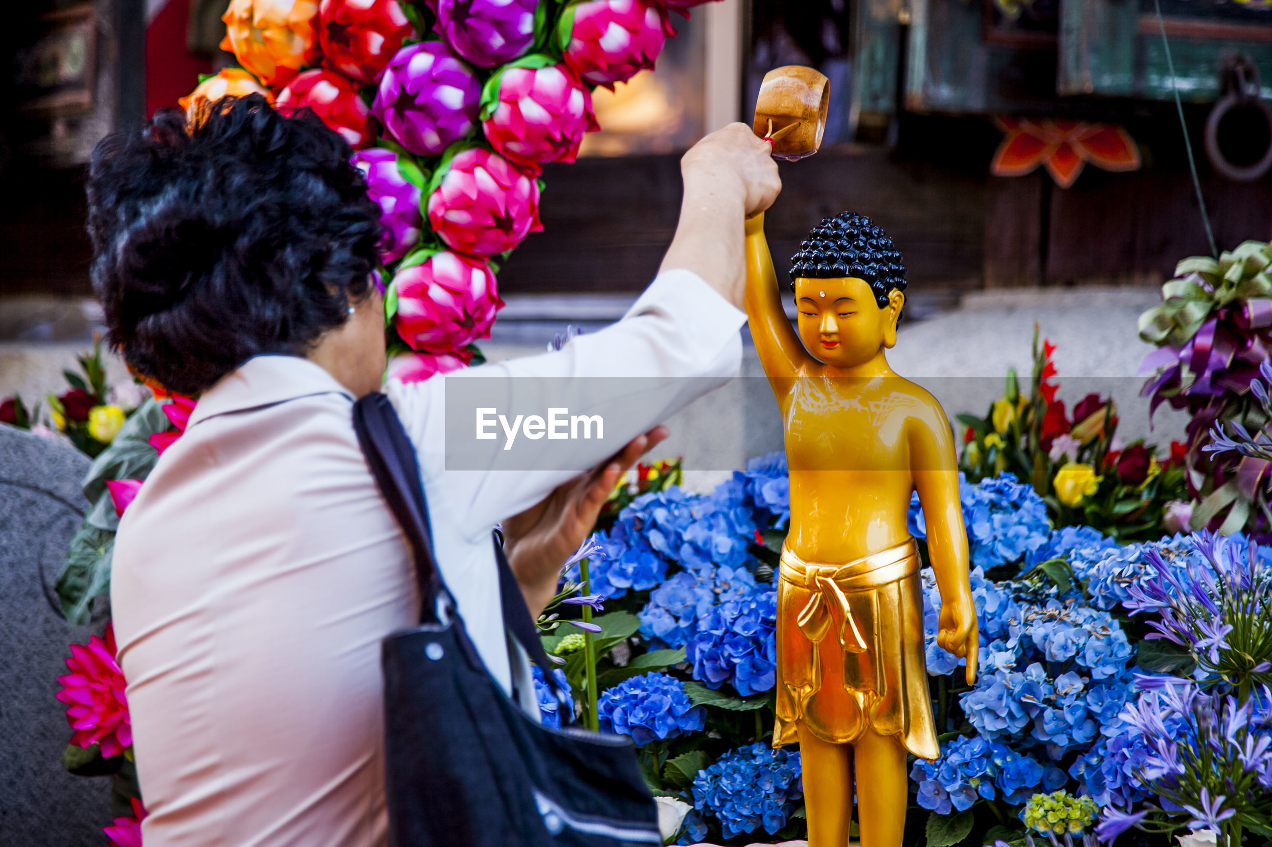 Rear view of woman worshipping buddha statue outdoors