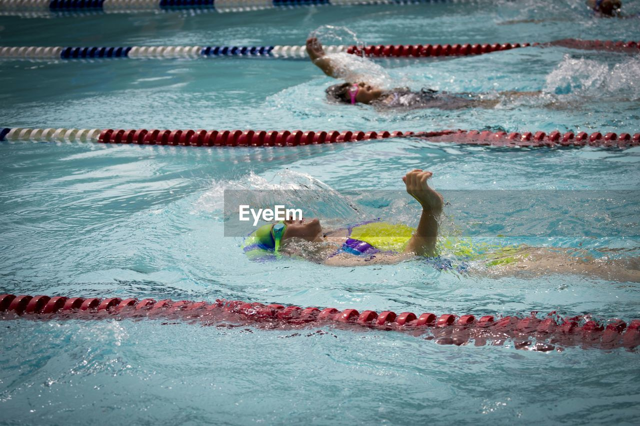 water, swimming, pool, sport, swimming pool, competition, swimming lane marker, athlete, sports race, motion, determination, nature, swimming cap, competitive sport, swimwear, healthy lifestyle, group of people, aquatic sport, people, outdoors, eyewear, skill, effort
