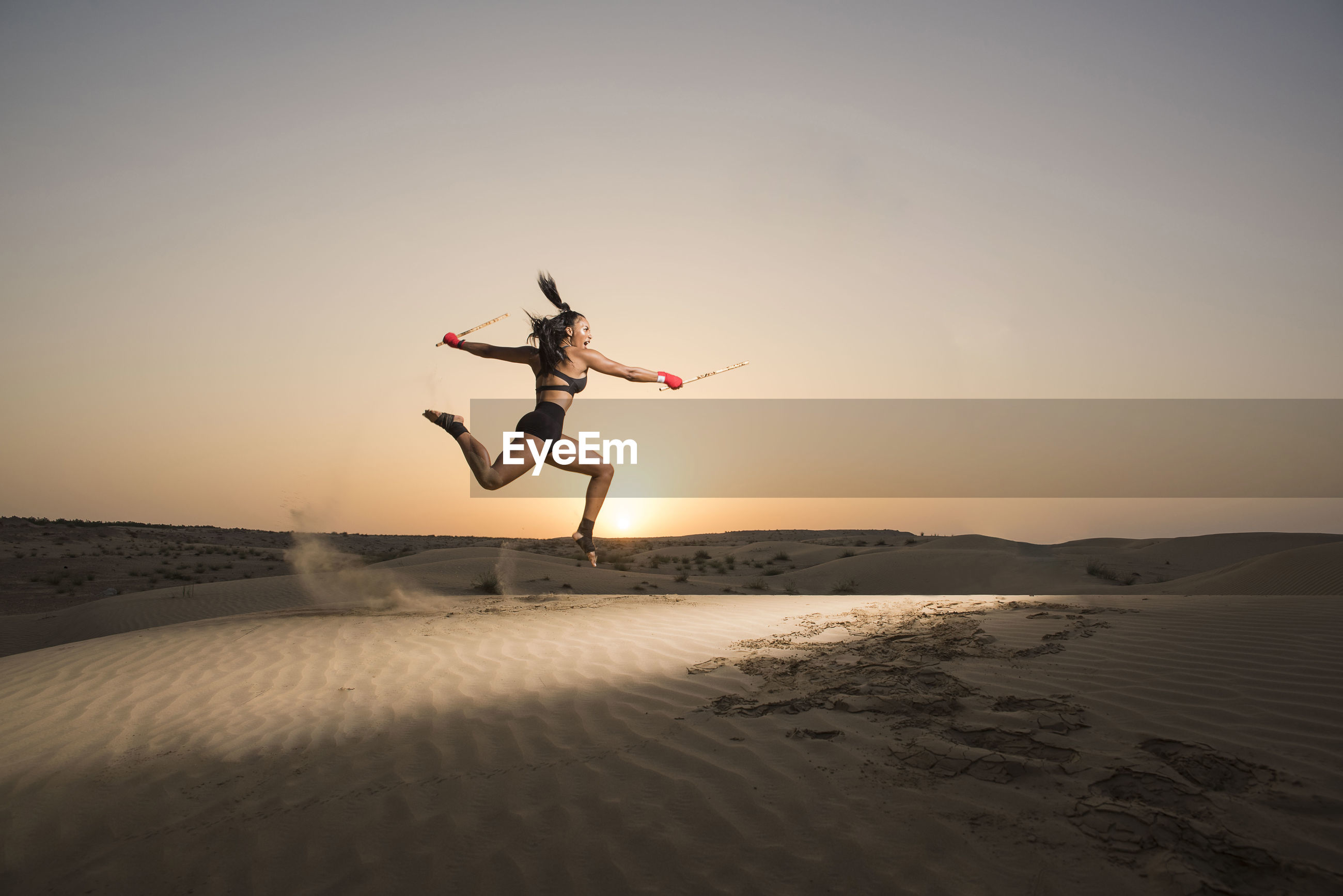 Young woman jumping on sand against sky