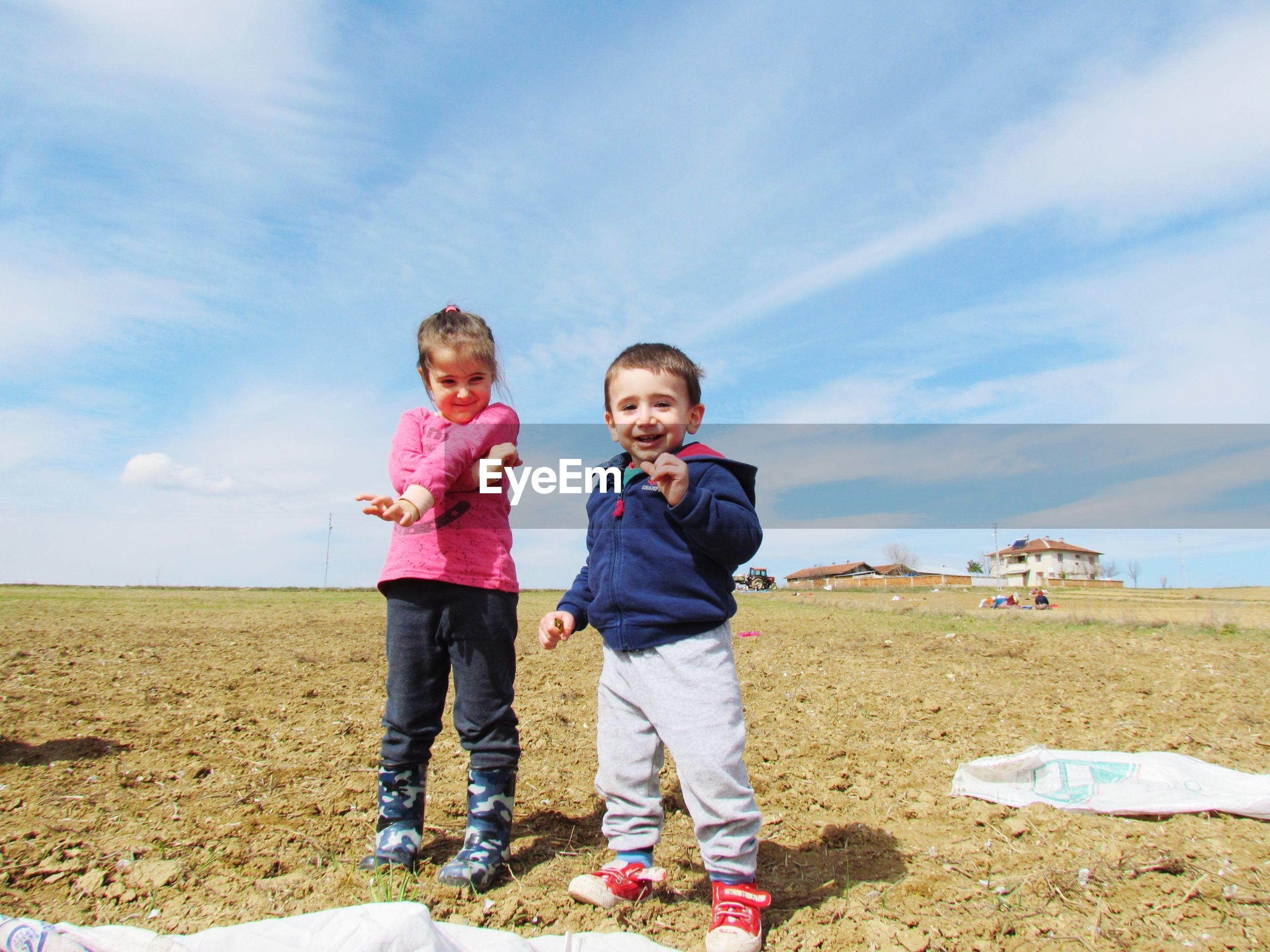 Portrait of happy siblings playing on field against sky