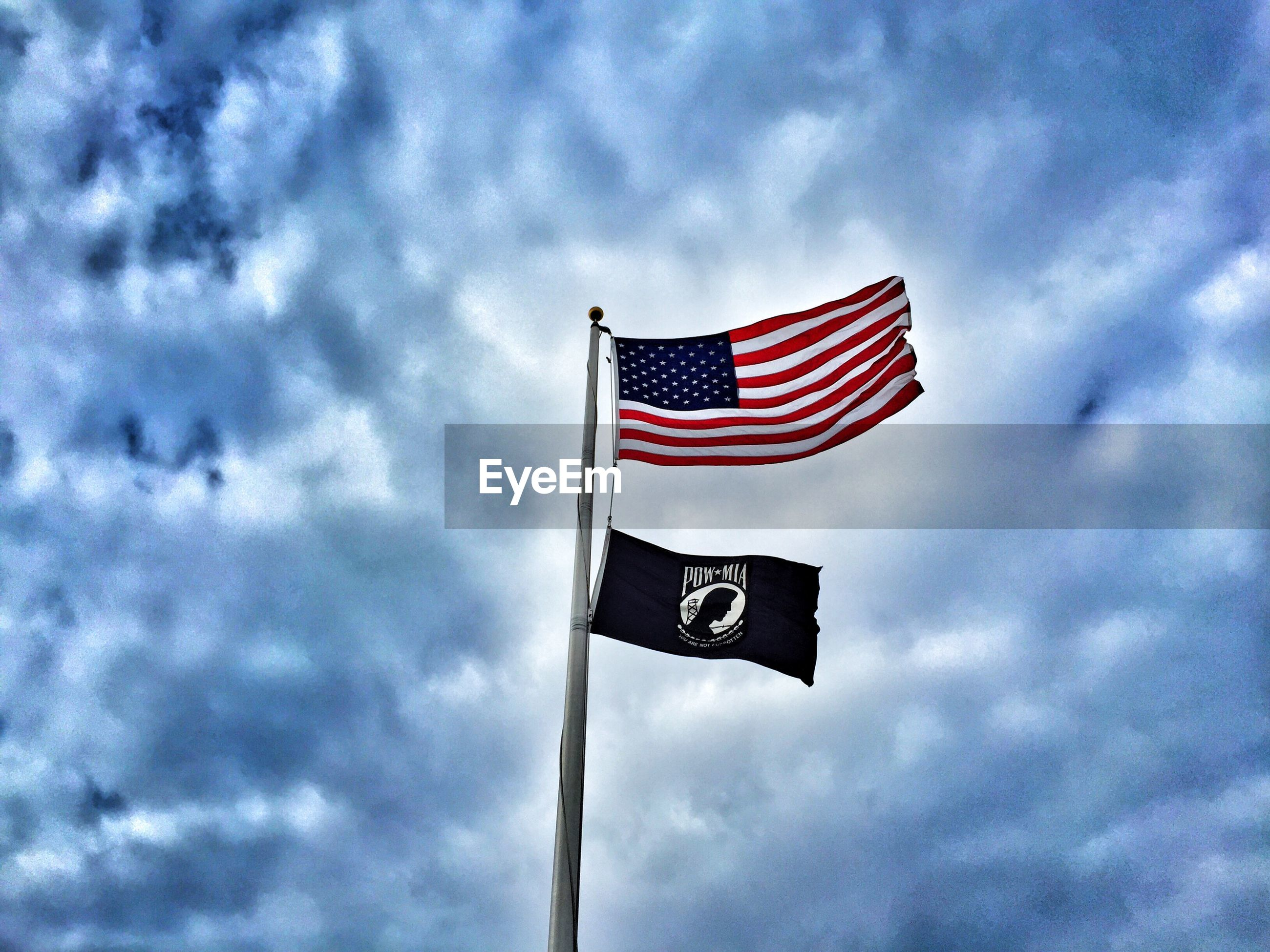 LOW ANGLE VIEW OF AMERICAN FLAG FLYING AGAINST CLOUDY SKY