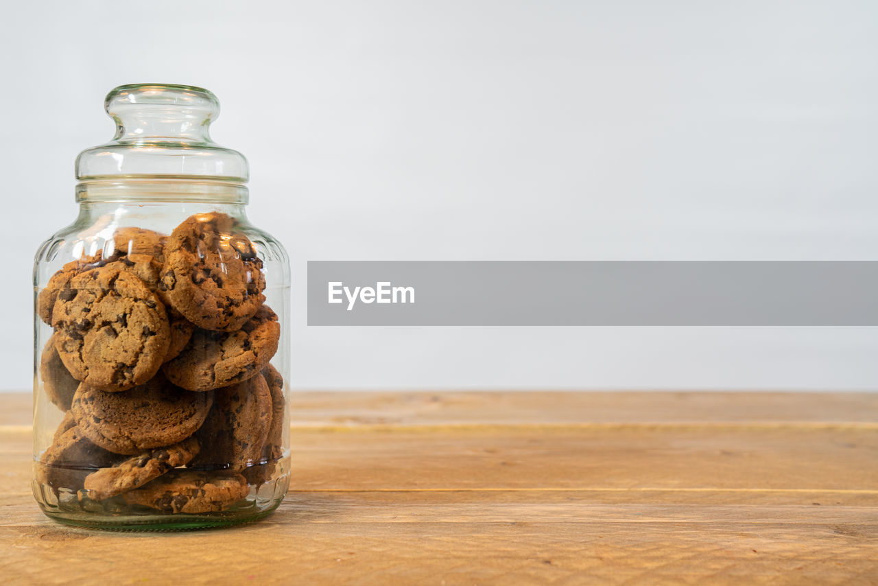 jar, table, still life, container, indoors, food and drink, cookie, glass - material, close-up, food, no people, cork - stopper, baked, wood - material, sweet food, transparent, copy space, temptation, indulgence, focus on foreground, snack