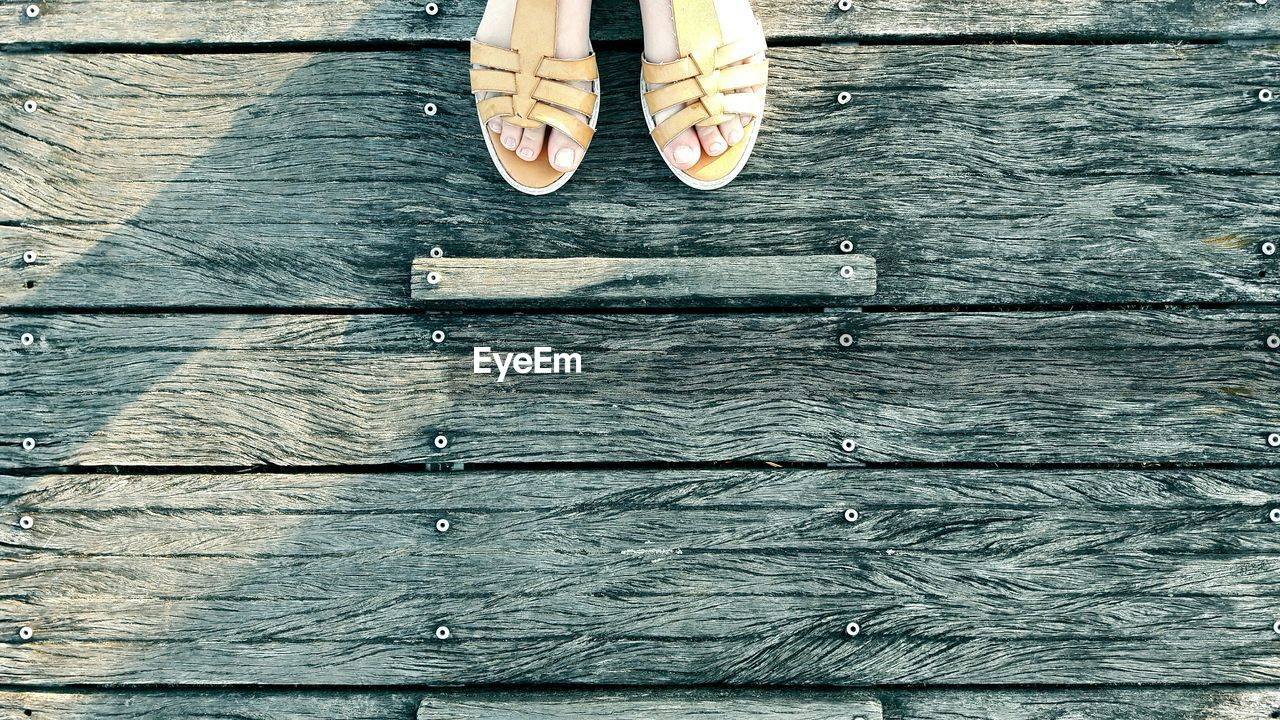 human leg, low section, wood - material, human body part, human foot, shoe, standing, directly above, real people, outdoors, day, lifestyles, one person, close-up, adult, people
