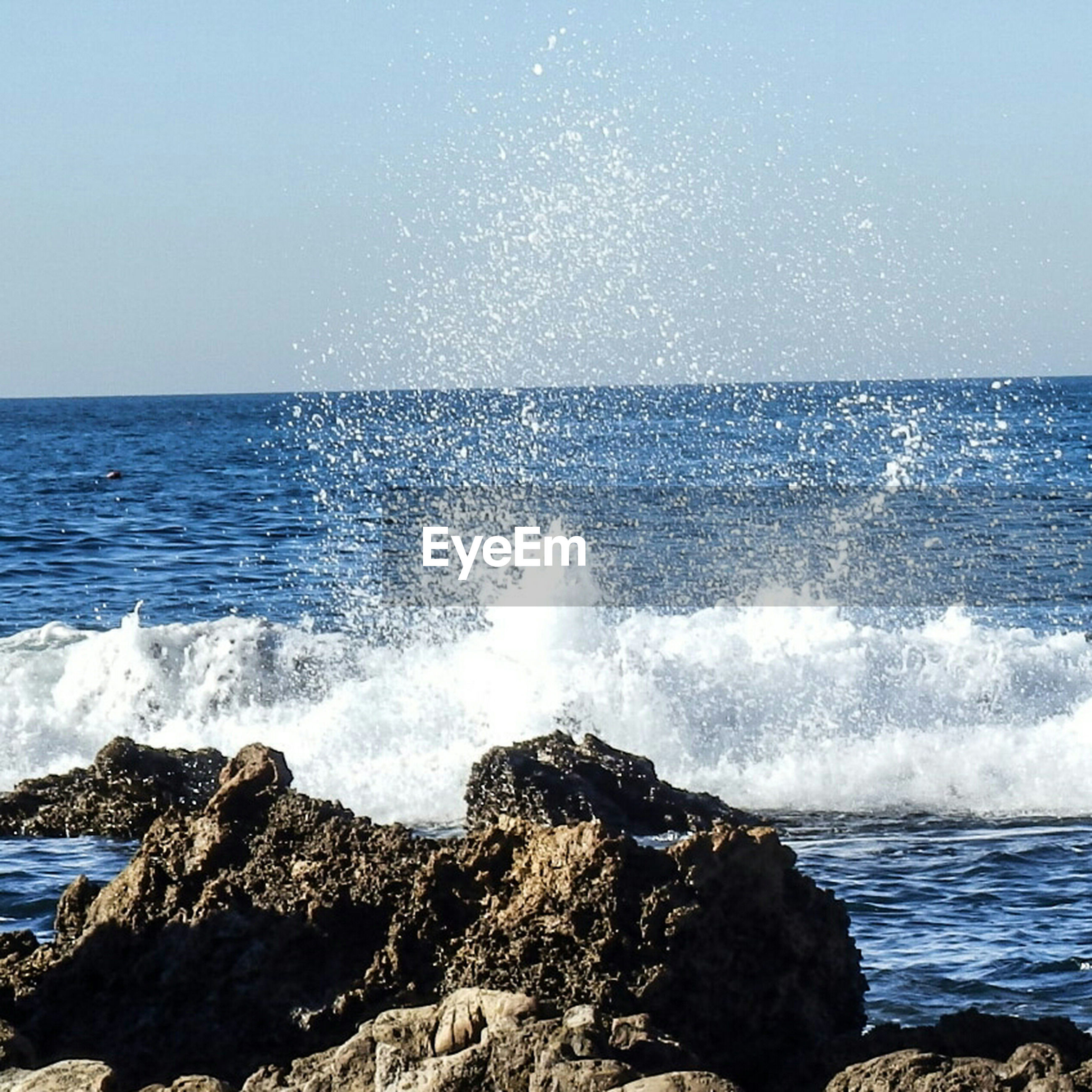 sea, horizon over water, water, beauty in nature, nature, wave, rock - object, scenics, motion, no people, outdoors, clear sky, rough, tranquil scene, sky, tranquility, breaking, day, beach, power in nature, crash, force, blue