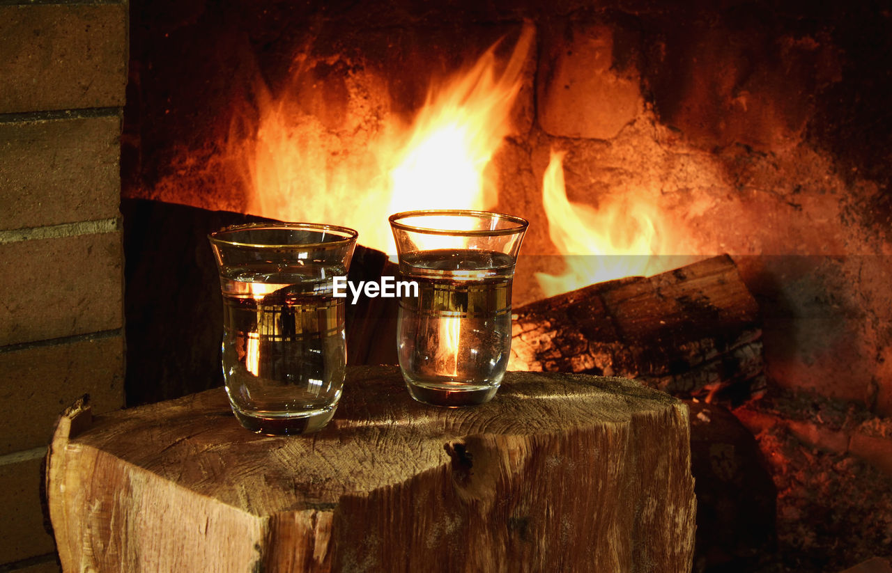 Close-Up Of Drinks In Glasses On Wood By Fireplace