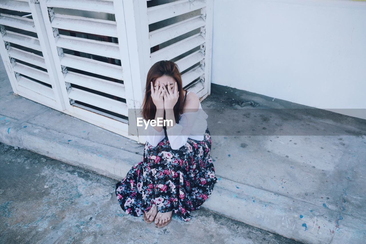 High Angle View Of Depressed Woman Sitting On Footpath