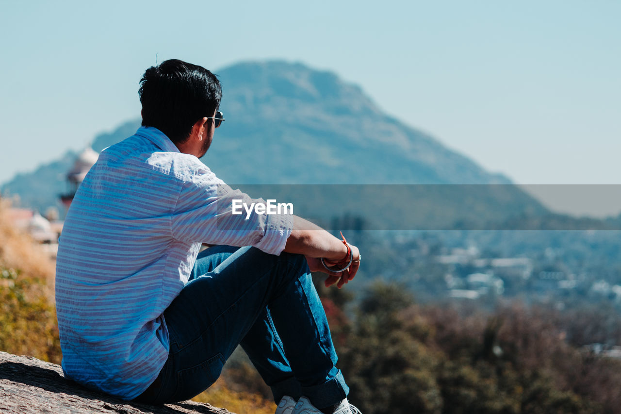 REAR VIEW OF YOUNG MAN LOOKING AT MOUNTAIN